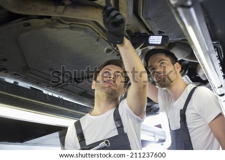 Male mechanics examining car in workshop - stock photo
