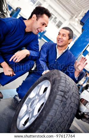 Male mechanics working as a team on car puncture - stock photo