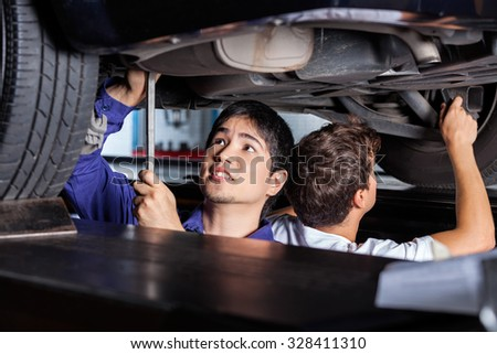 Male mechanics working under lifted car at garage - stock photo