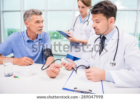 Male medical doctor taking mature patient blood pressure.