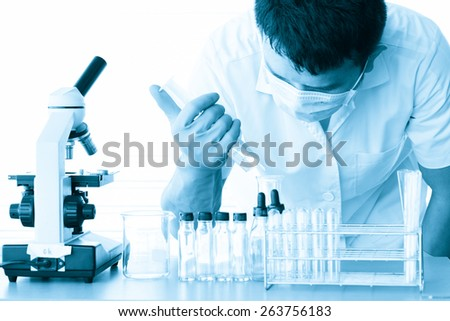 male medical or scientific researcher or man doctor looking at a test tube of clear solution in a laboratory with microscope beside men;effect cyanotype tone
