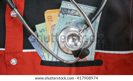 Male medicine doctor chest with bunch of hundred dollars banknotes in pocket closeup. Medic personnel salary, prestige and high paid job, education, public health business, medical insurance concept - stock photo