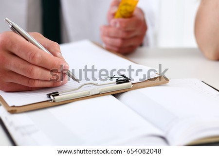 Male medicine doctor hand hold jar of pills and write prescription to patient at worktable.