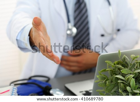Male medicine doctor offering hand to shake in office closeup. Greeting and welcoming friend, introduction or thanks gesture. Tests advertisement concept. Physician ready to examine patient - stock photo