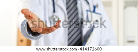 Male medicine doctor offering helping hand in office closeup. Friendly and cheerful gesture. Medical cure and tests advertisement concept. Physician ready to examine and save patient. Letterbox view - stock photo