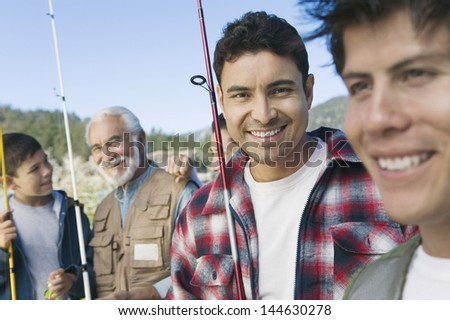 Male members of three generation family on fishing trip focus on mid adult man (portrait) - stock photo