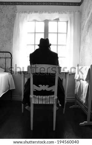 Male mental patient sitting in front of a window with hat and black coat, barefoot. - stock photo