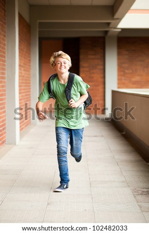 male middle school student running in school passage