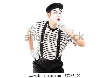 Male mime artist gesturing silence with a finger on his mouth, isolated on white background - stock photo