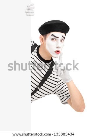 Male mime artist holding a blank panel and gesturing silence with a finger on his mouth, isolated on white background - stock photo