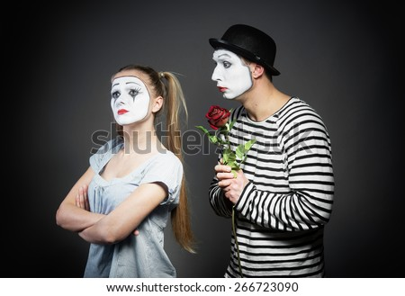 Male mime giving a flower to female mime - stock photo