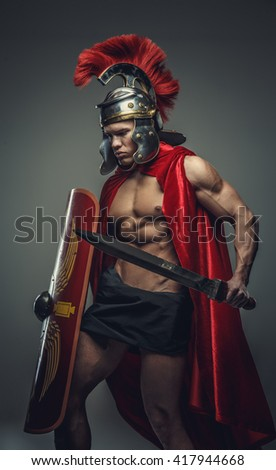 Male model in gladiator pose with sword and shield isolated on a grey background.