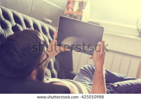 Male model lying on a couch in a living room, surfing the web on a tablet computer