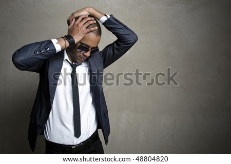 Male model poses in his sharp suit in front of grunge wall