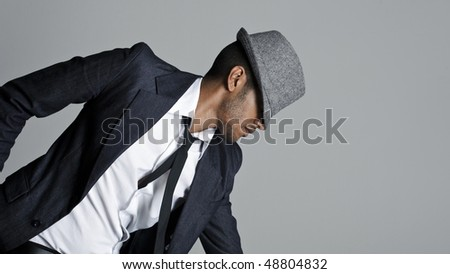 Male model poses in suit with his fedora over his face
