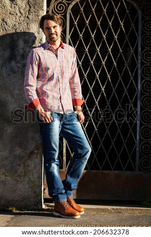 Male model relaxing leaning against wall with hands in pocket - stock photo