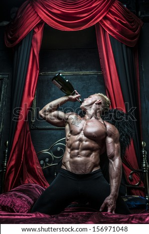 Male model Serge Henir with wings and a bottle - stock photo