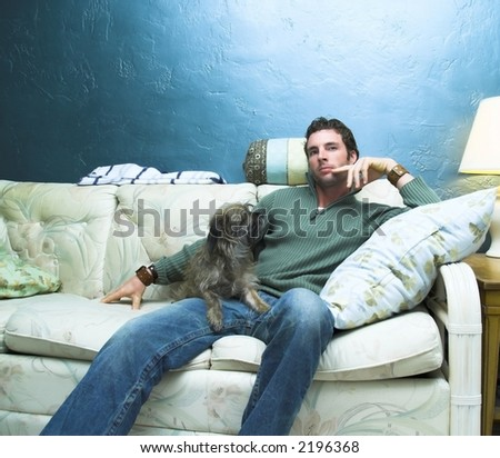 Male model sitting with his dog... - stock photo