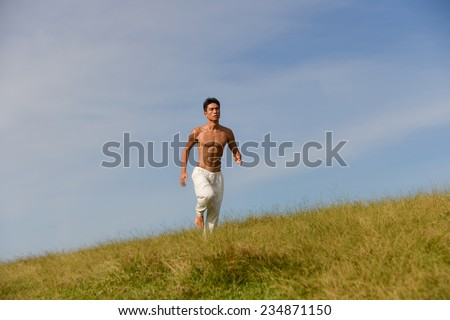 male model with muscles is running on summer meadow  - stock photo