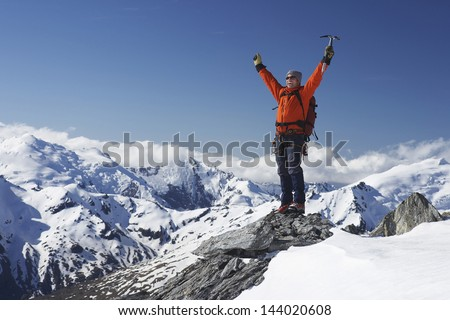 Male mountain climber raising hands with icepick on top of snowy peak - stock photo