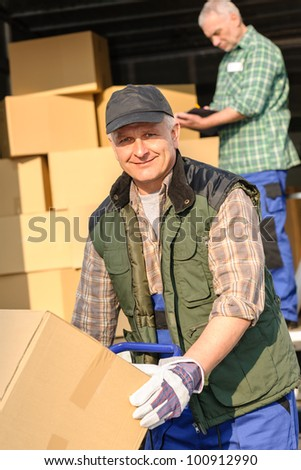 Male mover loading van with cardboard box delivery service - stock photo