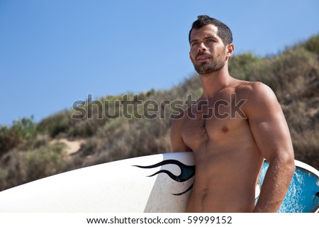 Male muscular surfer holding his board looking away - stock photo