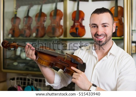 Male musician selecting violin in music instruments studio