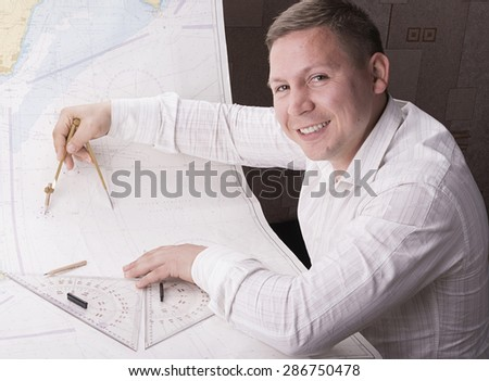 male navigator is measuring with divider on navigation map - stock photo