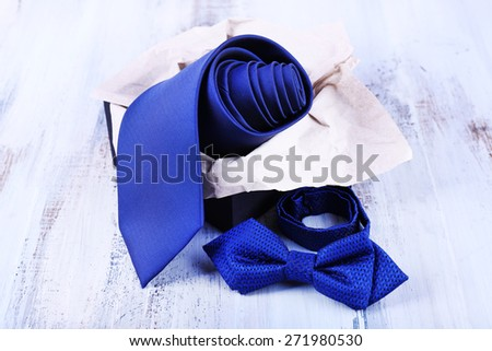 Male necktie and bow tie in box on wooden background - stock photo