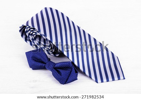 Male necktie and bow tie on wooden table background - stock photo