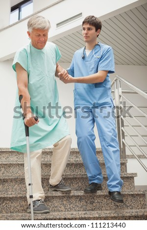 Male nurse assisting a patient in hospital stairs - stock photo