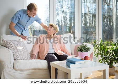 Male nurse caring about patient at home - stock photo