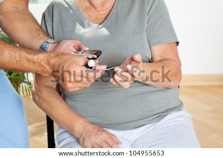 Male nurse checking sugar level of patient through glucometer
