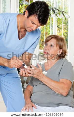 Male nurse checking sugar level of patient through glucometer - stock photo