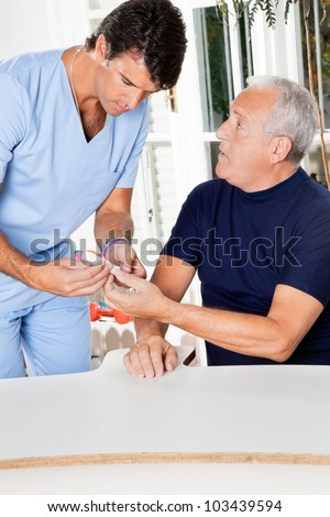 Male nurse checking sugar level of senior man through glucometer - stock photo