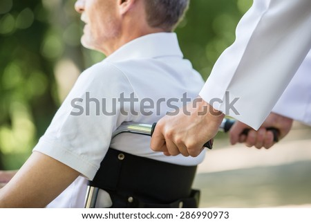 Male nurse walking with senior patient in wheelchair in garden near hospital. Close-up.