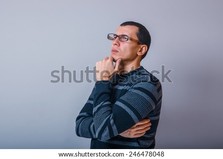male of European appearance brunet holding hand on chin thinking on a gray background, thoughts - stock photo