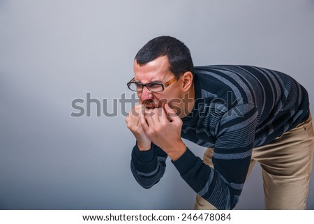 male of European appearance brunet put fingers in his mouth on a gray background - stock photo