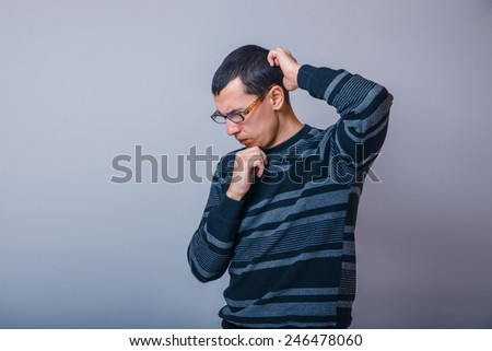 male of European appearance brunet thinking on a gray background, meditation - stock photo