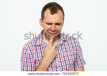 male of European appearance causes vomiting putting his fingers in his mouth on a gray background, nausea