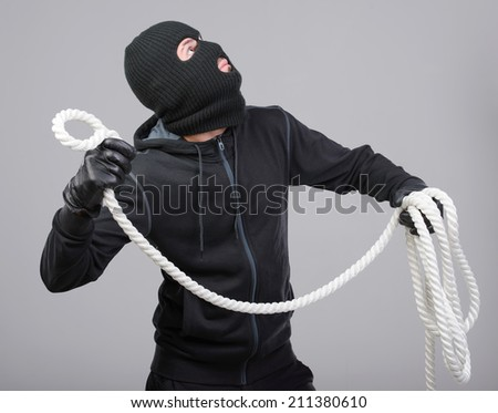 Male offender from Balaklava in the head with a rope.  - stock photo