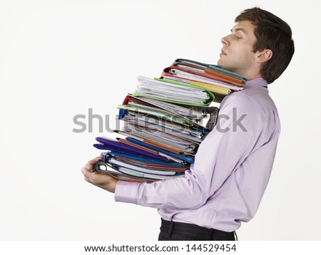 Male office worker carrying heavy binders against white background - stock photo