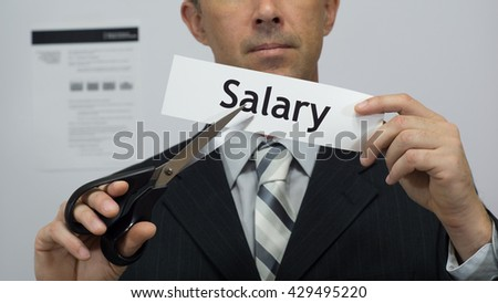 Male office worker or businessman in a suit and tie cuts a piece of paper with the word salary on it as a salary or pay reduction business concept. - stock photo