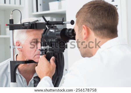 Male optician examining senior patients eyes through slit lamp in clinic - stock photo