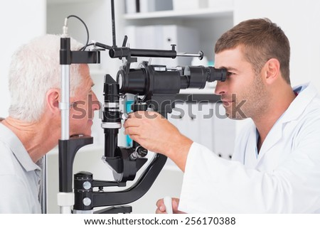 Male optometrist examining senior patients eyes through slit lamp in clinic