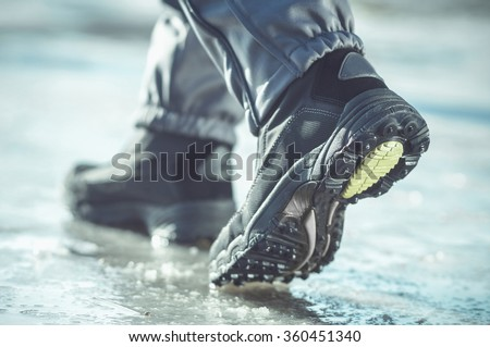 male or female winter boots walking on snowy sleet road. toned cold image - stock photo