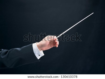 male orchestra conductor directing with his baton - stock photo