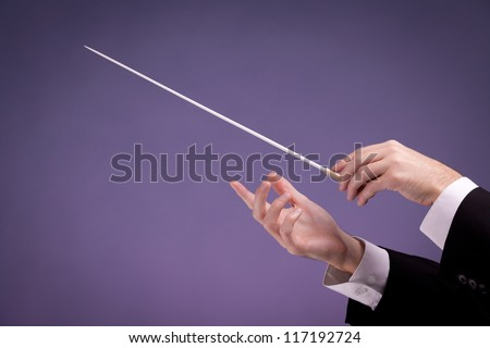 Male orchestra conductor hands, one with baton. Purple background. - stock photo