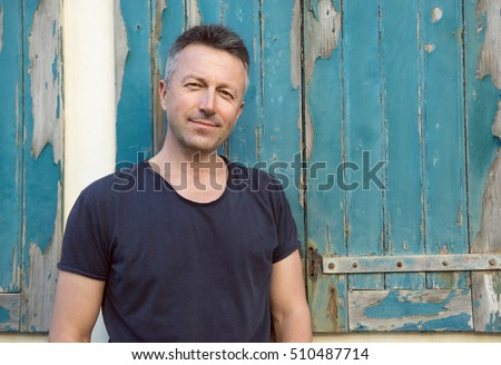 Male outdoor street portrait. Mid adult man over grunge wall and windows.