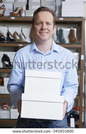 Male Owner Of Shoe Store Carrying Boxes
